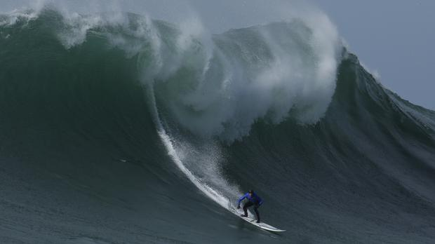 Travis Payne rides a giant wave during the finals of the Mavericks surfing contest in California's Half Moon Bay (Ben Margot/AP)