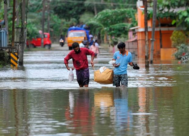 Men carry supplies to those stranded by floods in Pandanad – more than one million people have swarmed relief camps in India's Kerala state to escape monsoon floods. Photo: Getty