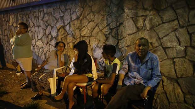 Residents sit outside their apartments in a street near the Tower of David (AP)
