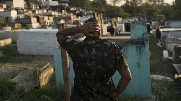 A soldier attends the burial of Joao Viktor da Silva in Japeri (Leo Correa/AP)