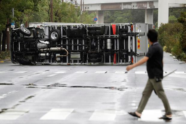 A man looks at a truck overturned following a powerful typhoon in Osaka. AP