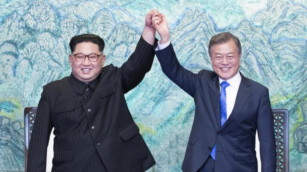 North Korean leader Kim Jong Un and South Korean president Moon Jae-in raise their hands after signing on a joint statement at the border village of Panmunjom in April (Korea Summit Press/AP)