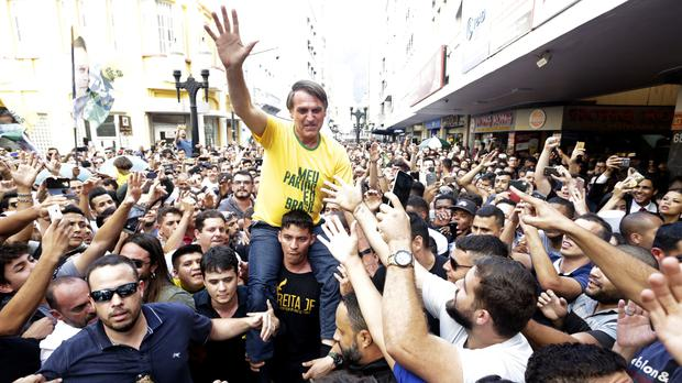 Presidential candidate Jair Bolsonaro is taken on the shoulders of a supporter moments before being stabbed during a campaign rally in Juiz de Fora (Antonio Scorza/Agencia O Globo via AP)