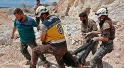 Members of the Syrian Civil Defence carry a victim after attacks near Idlib province. Photo: Getty Images