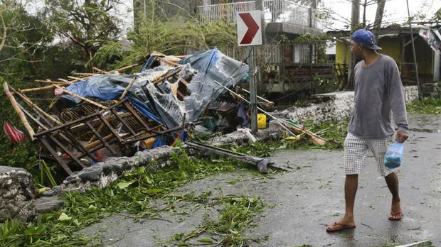 A man looks at a damaged house due to strong winds from Typhoon Mangkhut as it barrelled across Tuguegarao city in Cagayan province, northeastern Philippines (AP Photo/Aaron Favila)