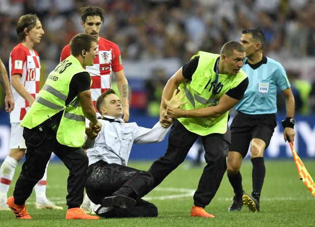 Stewards pull Pyotr Verzilov, a member of the feminist protest group Pussy Riot off the pitch (Martin Meissner/AP)