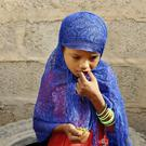 A girl eats boiled leaves from a local vine to stave off starvation in Yemen (AP Photo/Hammadi Issa)