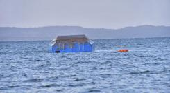 The upturned passenger ferry MV Nyerere floats in the water near Ukara Island in Lake Victoria (AP)
