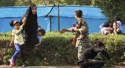 A woman takes her children to shelter as an army member tries to help them, during a shooting at the military parade (Fatemeh Rahimavian/Fars News Agency via AP)