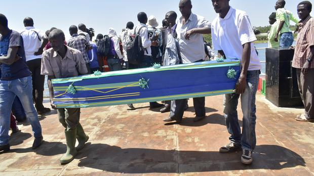 Relatives carry coffins to be used for the victims of the MV Nyerere passenger ferry disaster (Andrew Kasuku/AP)