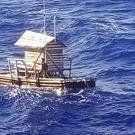 Aldi Novel Adilang is seen on a wooden fish trap floating in the waters near the island of Guam (Indonesian Consulate General in Osaka via AP)