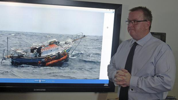 Australian Maritime Safety Authority response centre manager Alan Lloyd in front of a photograph of Indian sailor Abhilash Tomy's yacht (Rod McGuirk/AP)