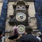 Tourists look at the medieval astronomical clock in Prague (Petr David Josek/AP)