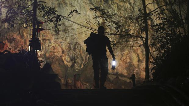 A rescuer makes his way down the entrance to the cave complex where 12 boys and their football coach went missing in Thailand (Sakchai Lali/AP)
