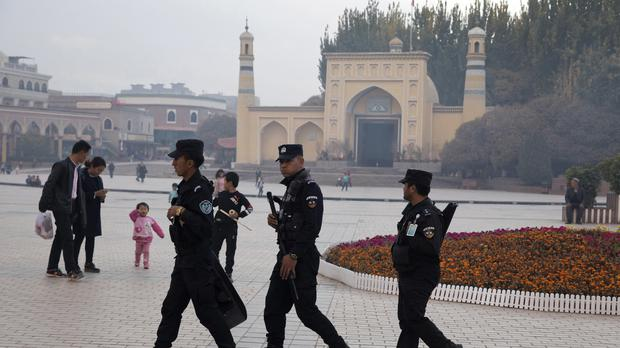 """FILE – In this Nov. 4, 2017 file photo, Uighur security personnel patrol near the Id Kah Mosque in Kashgar in western China's Xinjiang region. China's northwestern region of Xinjiang has revised legislation to allow the detention of suspected extremists in """"education and training centers."""" The revisions come amid rising international concern over a harsh crackdown in Xinjiang that has led to as many as 1 million of China's Uighurs and other Muslim minorities being held in internment camps. (AP Photo/Ng Han Guan, File)"""