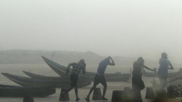 Indian fishermen prepare to leave the beach during rain and strong winds (AP)