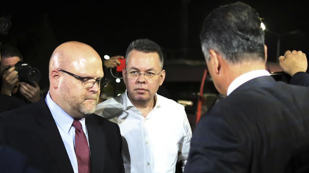 Andrew Brunson, centre, and US charge d'affaires Jeffrey Hovenier, left, arrive at Adnan Menderes airport for a flight to Germany (Emre Tazegul/AP)