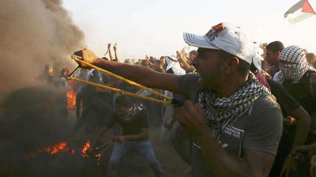 Protesters use slingshots to hurl stones while others burn tyres near the fence of the Gaza Strip border with Israel (Adel Hana/AP)