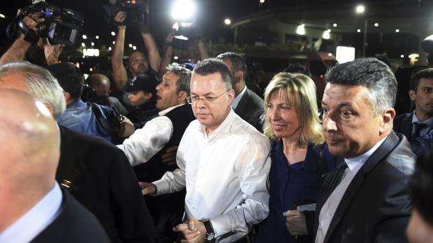 Andrew Brunson, centre left, and his wife Norine Brunson arrive at Adnan Menderes airport for a flight to Germany (Emre Tazegul/AP)