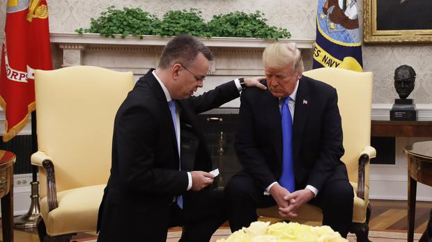 President Donald Trump prays with American pastor Andrew Brunson in the Oval Office (Jacquelyn Martin/AP)