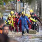 Rescue workers retrieve a body from floodwaters in the town of Trebes (Fred Lancelot/AP)