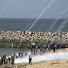 Teargas canisters fired by Israeli troops fall over Palestinians during a protest on a beach at the border with Israel near Beit Lahiya, northern Gaza Strip (Khalil Hamra/AP)