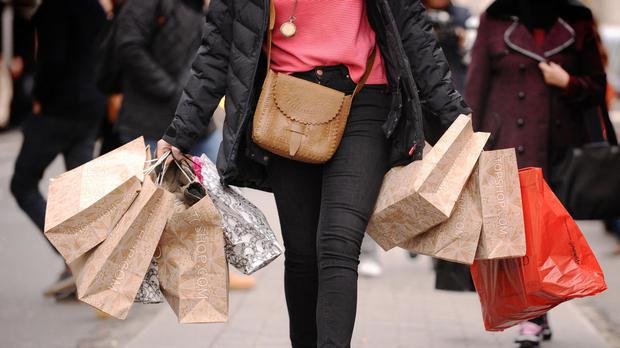 "File photo dated 06/12/11 of a woman carrying shopping bags. British retailers are bracing for a £320 million ""warm weather"" hit to their coffers next month as higher temperatures melt sales."