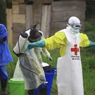 A health worker sprays disinfectant on his colleague after working at an Ebola treatment centre in Beni (Al-hadji Kudra Maliro/AP)