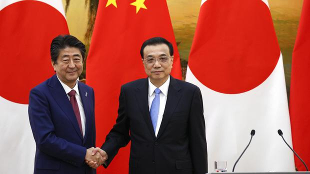 Japanese prime minister Shinzo Abe shakes hands with Chinese premier Li Keqiang (AP)