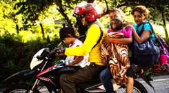 US Bound: A Honduran migrant family heading north on a motorbike in southern Mexico on October 25. Photo: Getty Images