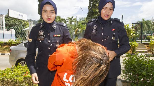 Samantha Jones is escorted by police as she arrives at Langkawi Magistrates' court in Langkawi,, Malaysia (AP)