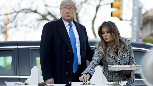 First lady Melania Trump, accompanied by President Donald Trump, puts down a white flower at a memorial for those killed at the Tree of Life Synagogue in Pittsburgh (Andrew Harnik/AP)