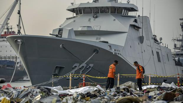 Members of National Search and Rescue Agency inspect debris retrieved from the waters (Fauzy Chaniago/AP)