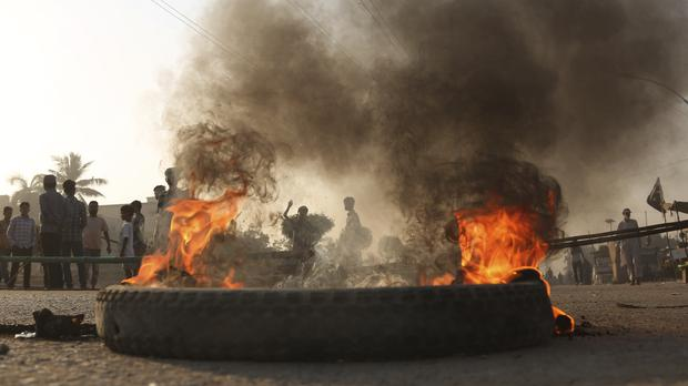 Protesters burn tyres after Asia Bibi was acquitted (Shakil Adil/AP)