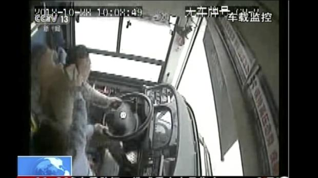 CCTV footage shows a passenger striking a bus driver with an object moments before it plunged off a bridge into the Yangtze River (CCTV via AP Video)