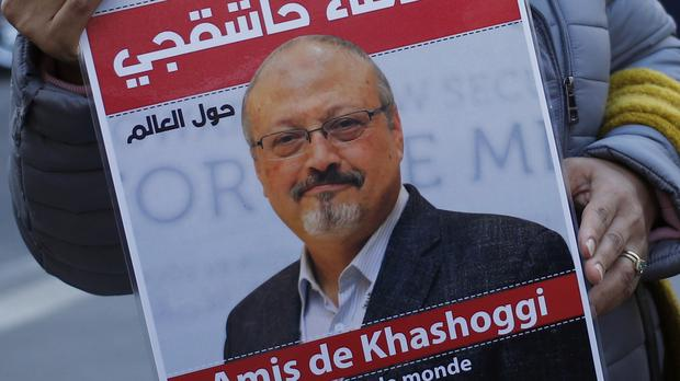 "An activist holds a portrait reading ""Friends of Khashoggi"" (AP Photo/Francois Mori)"