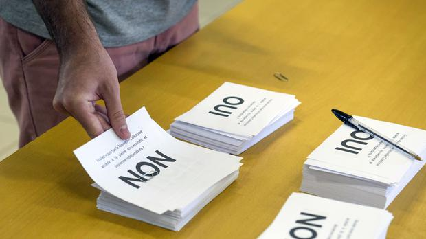 A man prepares to cast his vote at a polling station in Noumea (AP)