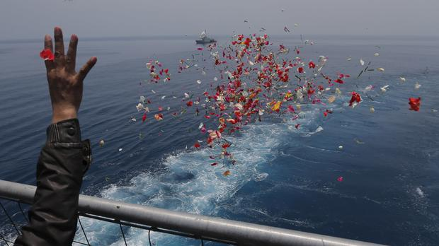 A relative sprinkles flowers during a prayer for the victims of the crashed Lion Air flight 610 (Tatan Syuflana/AP)