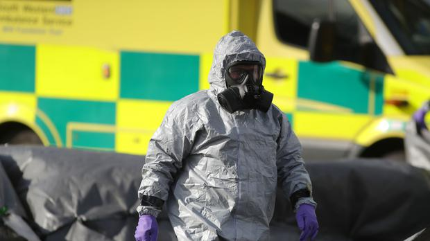 Investigators in masks examine an ambulance after the Skripal poisoning (Andrew Matthews/PA)