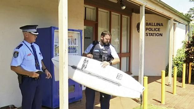 Police hold a victim's surfboard at a police station in Ballina (ABC/AP)