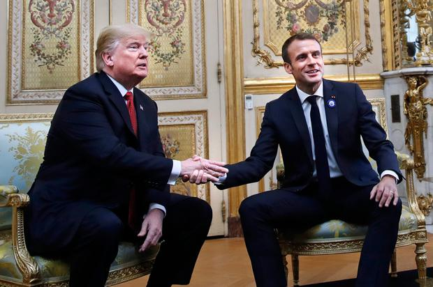 President Donald Trump shakes hands with French President Emmanuel Macron inside the Elysee Palace. Photo: AP