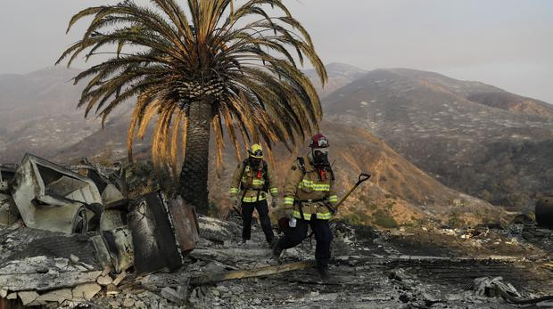 Firefighters walk among the ashes of a wildfire-ravaged home in Malibu (Marcio Jose Sanchez/AP)