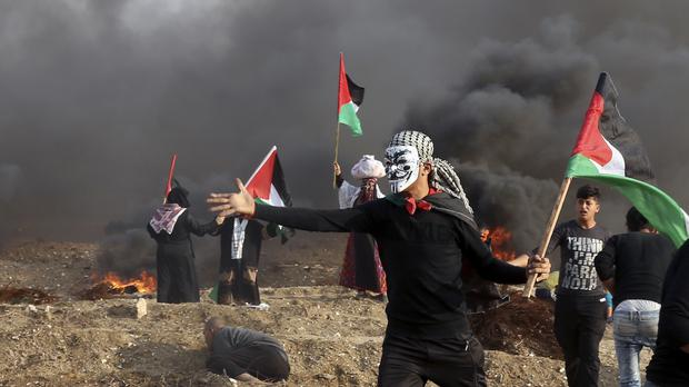 Protesters wave their national flags while others burn tyres near the Gaza Strip border with Israel (Adel Hana/AP)