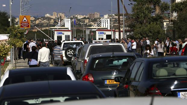 Greek Cypriots wait in their cars to use a newly-opened crossing point (Petros Karadjias/AP)