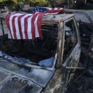 An American flag is draped over the charred remains of an old pickup (AP Photo/Richard Vogel)
