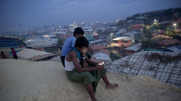 Rohingya Muslims use their mobile phones as they sit on a hill overlooking Balukhali refugee camp (Dar Yasin/AP)