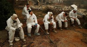 Grim task: Members of the California National Guard take a break as they search for human remains in Paradise, California. Photo: AP