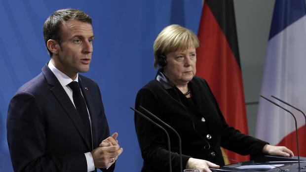 Angela Merkel and Emmanuel Macron during a joint statement prior to a meeting at the chancellery in Berlin (Michael Sohn/AP)