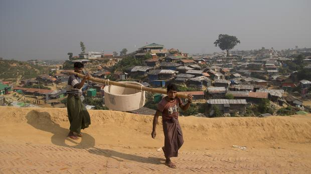 Rohingya refugees carry a hume pipe for construction of toilets inside Balukhali refugee camp near Cox's Bazar, in Bangladesh (Dar Yasin/AP)