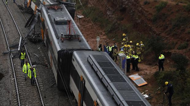 Firefighters and emergency workers stand by the derailed cars of a commuter train that went off the tracks near Barcelona (Emilio Morenatti/AP)